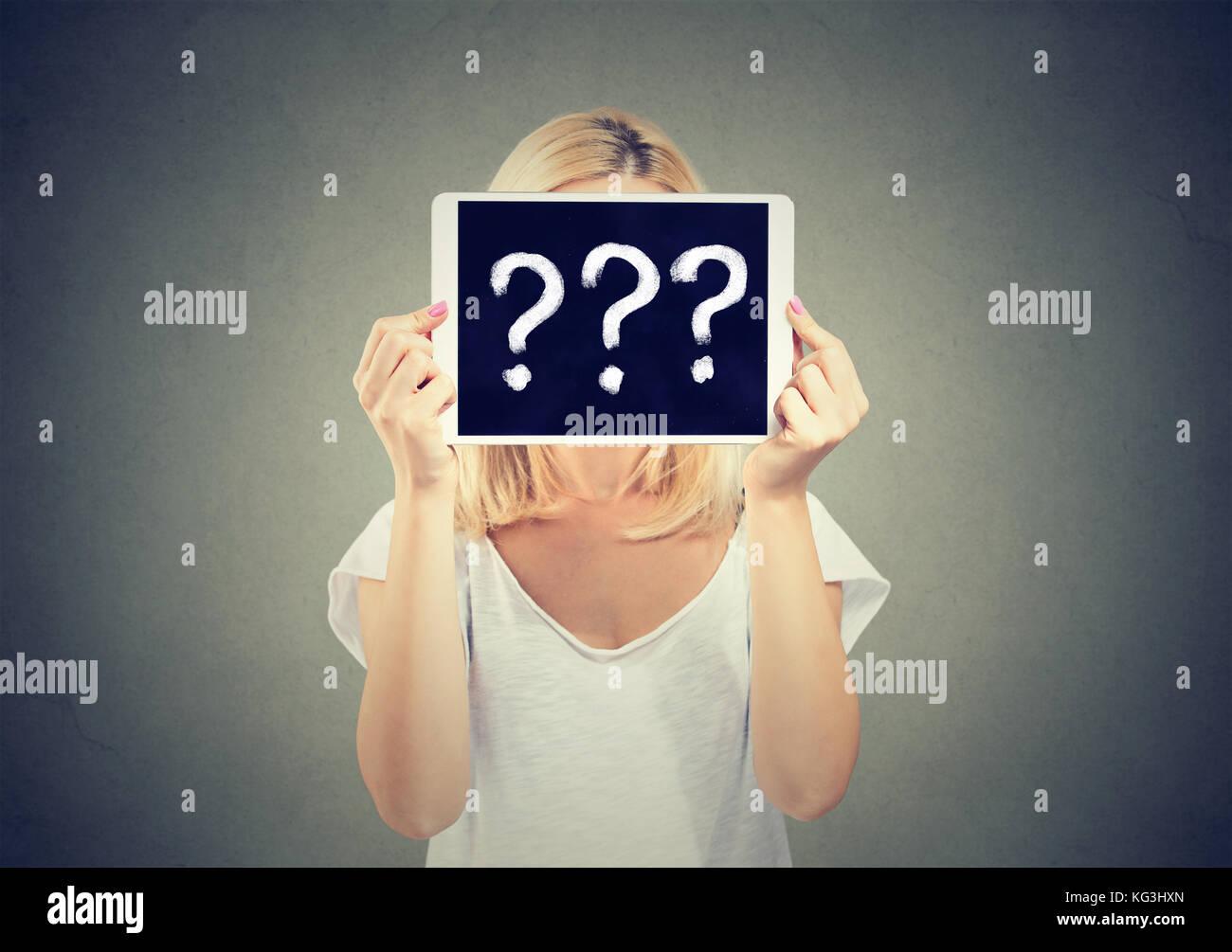 Donna che mantiene un tablet PC con un punto interrogativo per nascondere il suo volto isolato su sfondo grigio. Immagini Stock