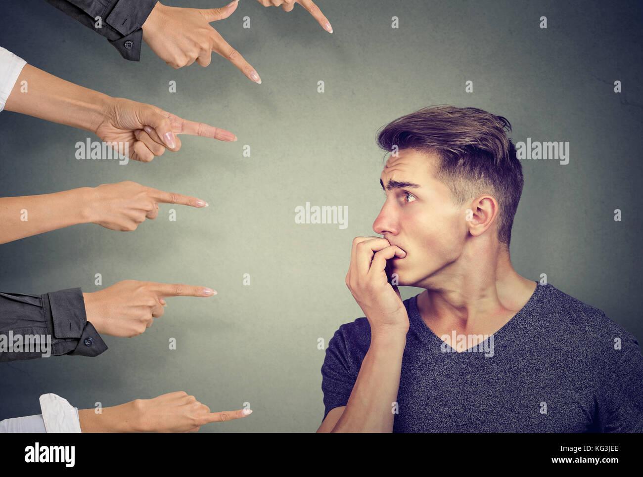 Ansiosi uomo giudicato da diverse persone. concetto di accusa di colpevole guy. negativa emozioni umane faccia sensazione Immagini Stock