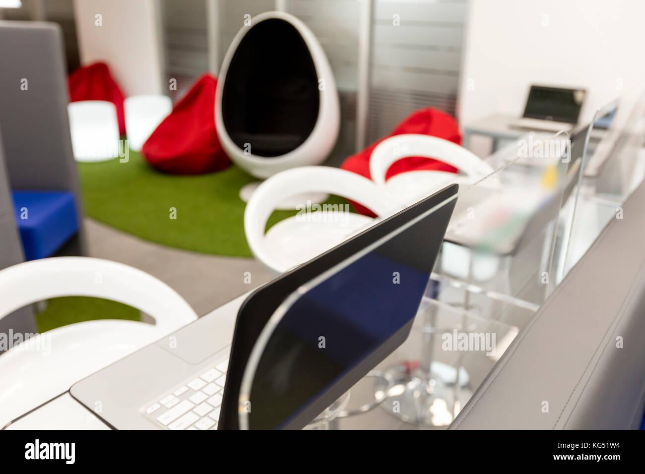 Ufficio moderno spazio con scrivania e computer portatili; lo spazio lounge in background. Immagini Stock