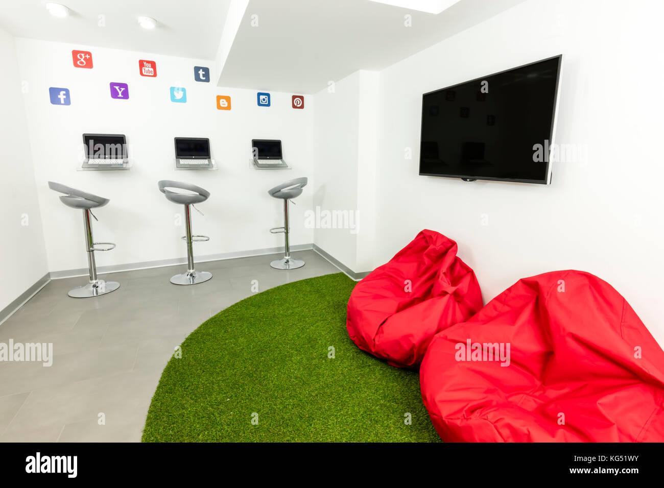 Moderno, in attesa o salotto; i laptop, tv e beanbags in background. Immagini Stock