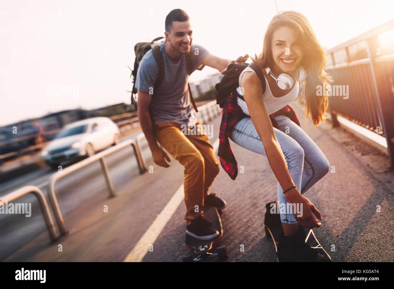 Giovane coppia attraente skateboard equitazione e divertimento Immagini Stock