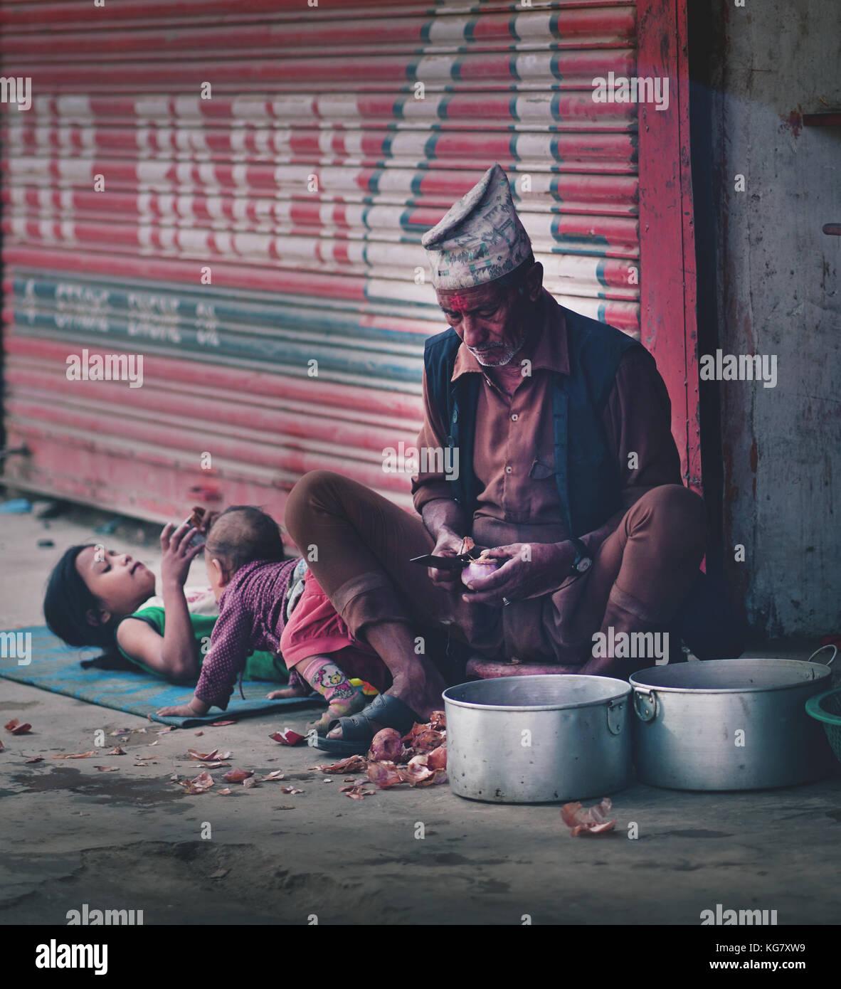 Il vecchio uomo nepalese Sbucciare le cipolle rosse accanto a due dei suoi nipoti a thamel street Immagini Stock