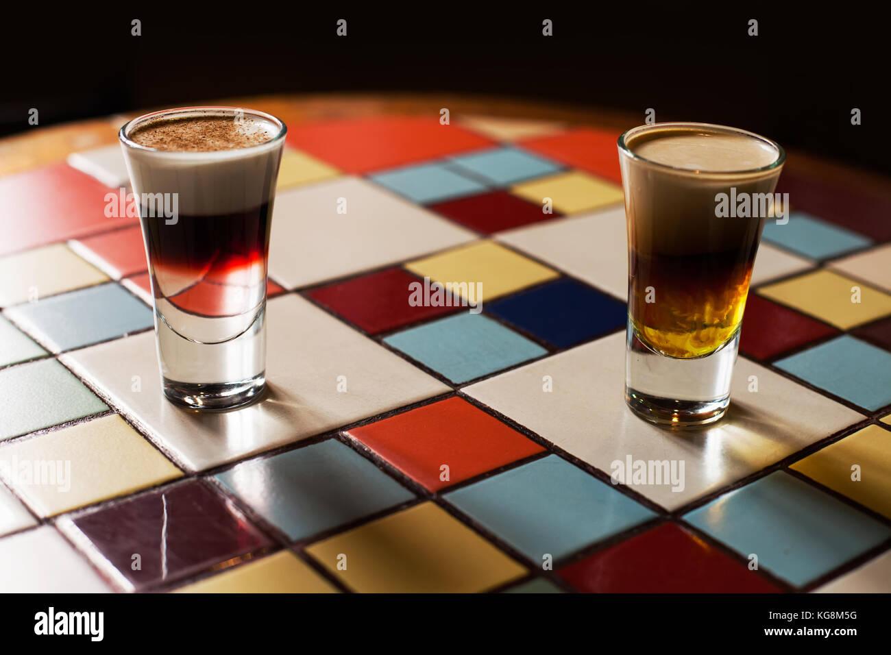 Festa Serale scatti alcoliche bevande, puffy cocktail in piccoli bicchieri su piastrelle multicolori tabella. Messa Immagini Stock