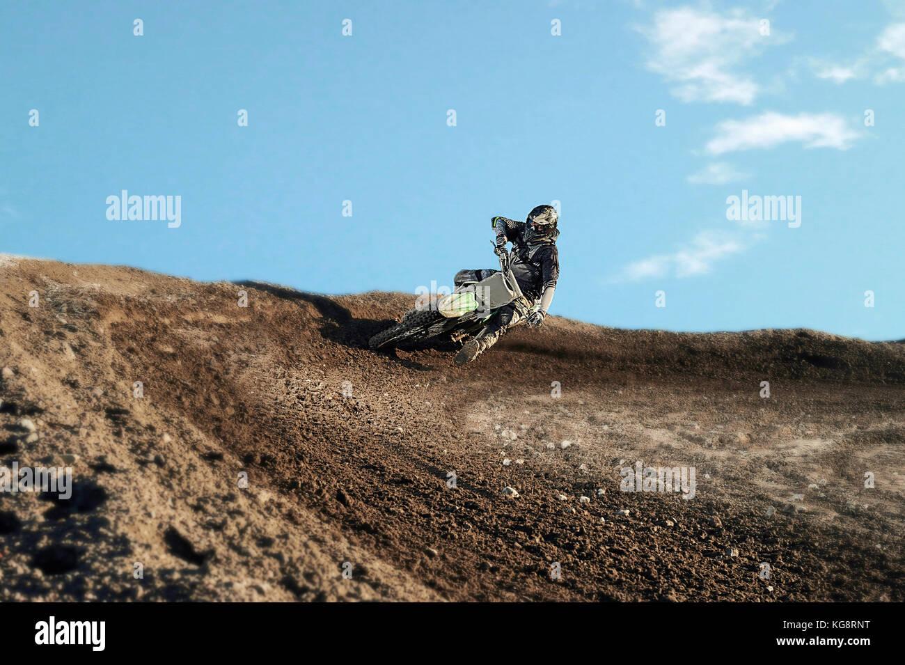 Driver di motocross in azione accelerando la moto dopo l'angolo sulla pista Immagini Stock