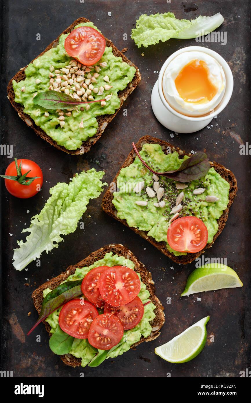Verde sano veggie toast con avocado, pomodoro, i germogli e i semi e uova sode su sfondo arrugginito. Tabella vista Immagini Stock