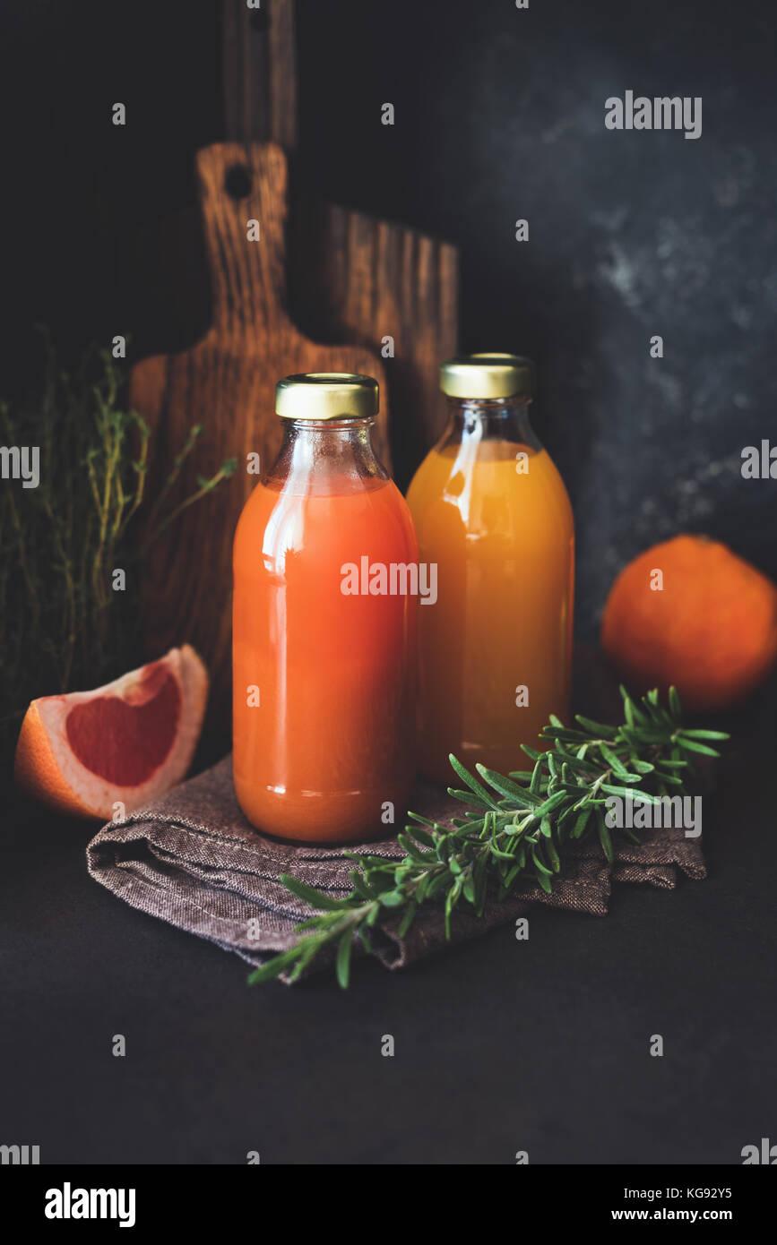 Agrumi freschi succhi di frutta in bottiglia. Pompelmo e arancia spremuta di frutta fresca con polpa, sana detox Immagini Stock
