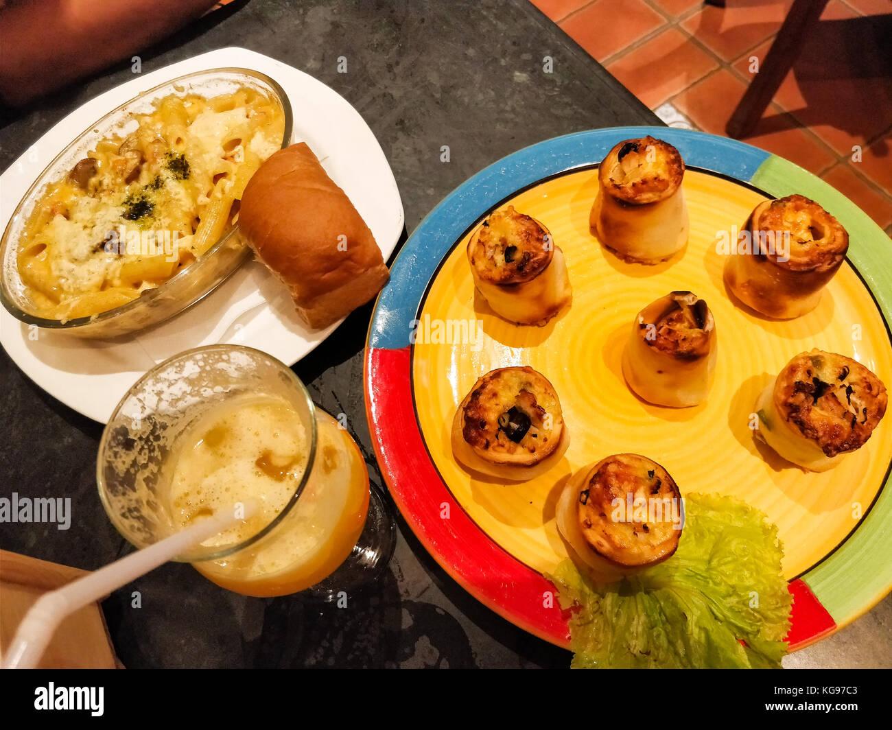 Brunch italiano con poppers, lasagne, pane all'aglio e mocktail drink servito su piastre colorate Immagini Stock