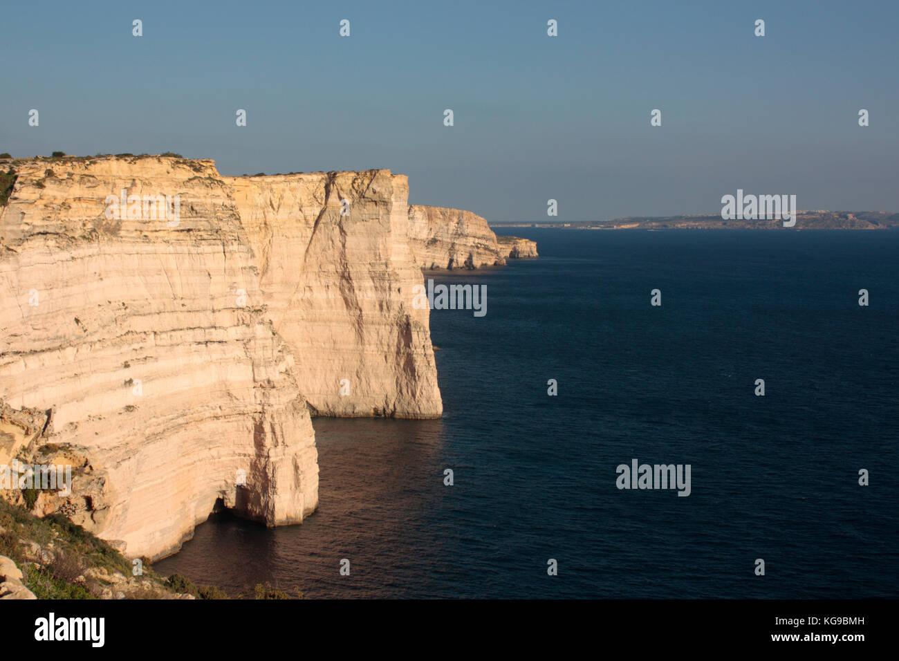 Scogliere Sanap, Gozo, con Comino e Malta visibile in distanza Immagini Stock