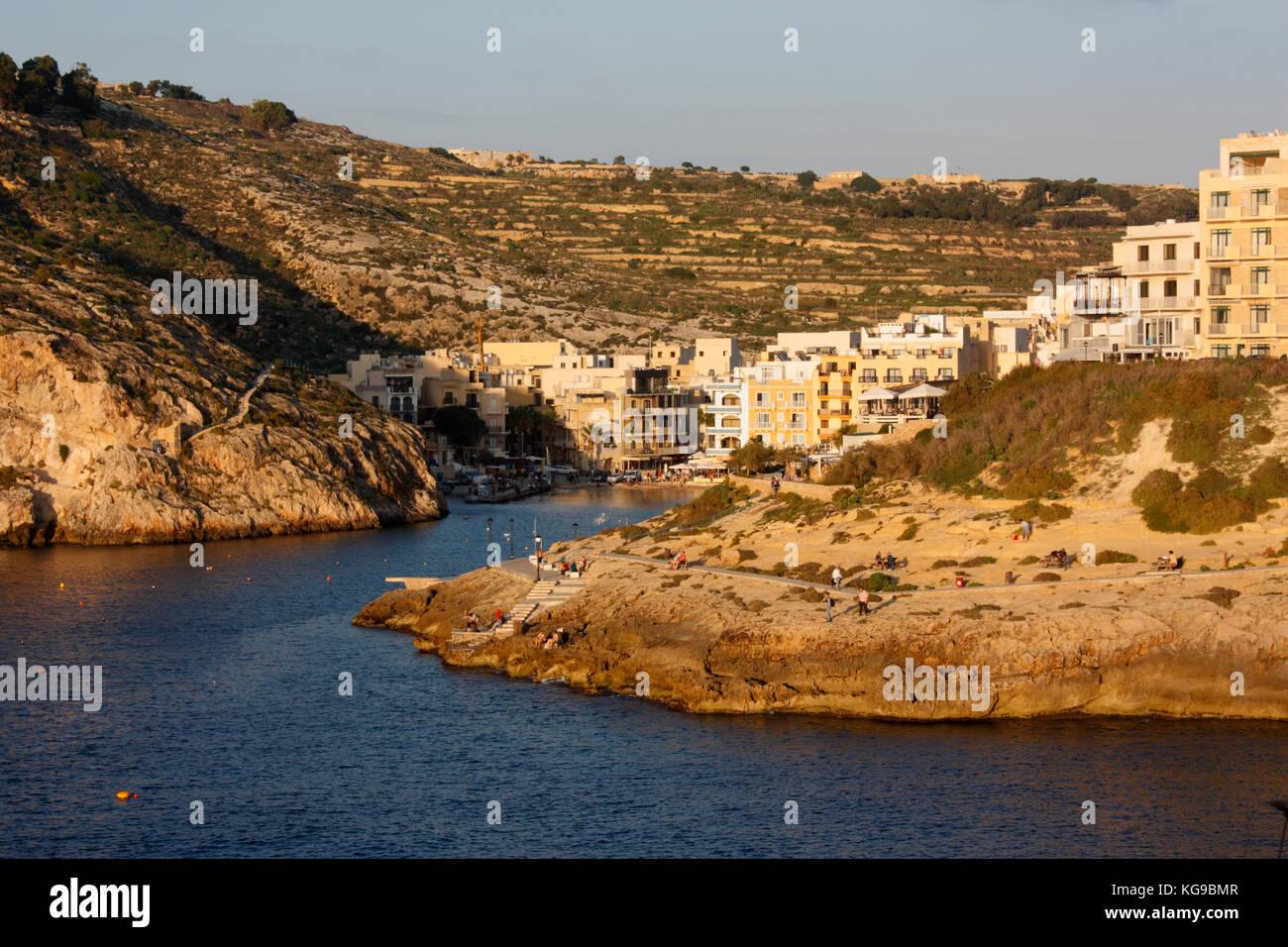 Il villaggio sul mare di Xlendi (pronunciato Shlendy) a Gozo, Malta, al tramonto Immagini Stock