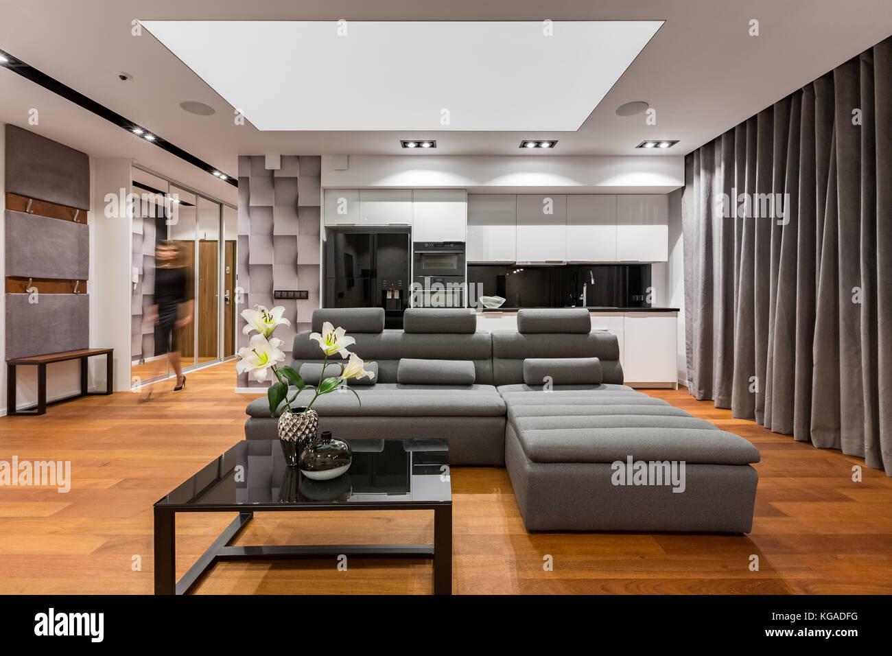 Soggiorno con strette grigio divano, tavola nera e angolo ...