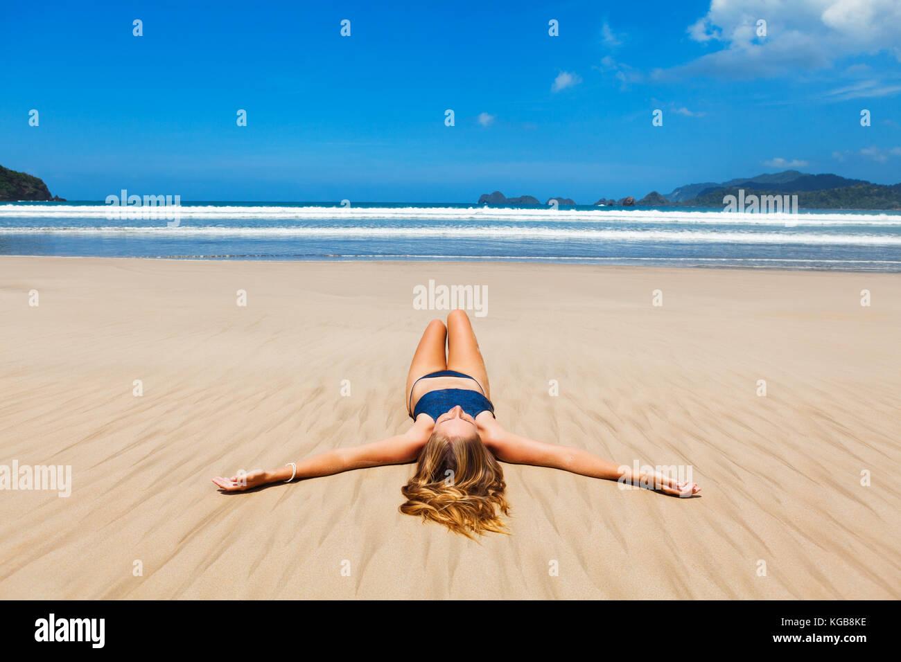 Donna felice in bikini rilassarsi e godersi il sole sulla spiaggia con mare surf. Sdraiati sulla sabbia, diffondere Immagini Stock