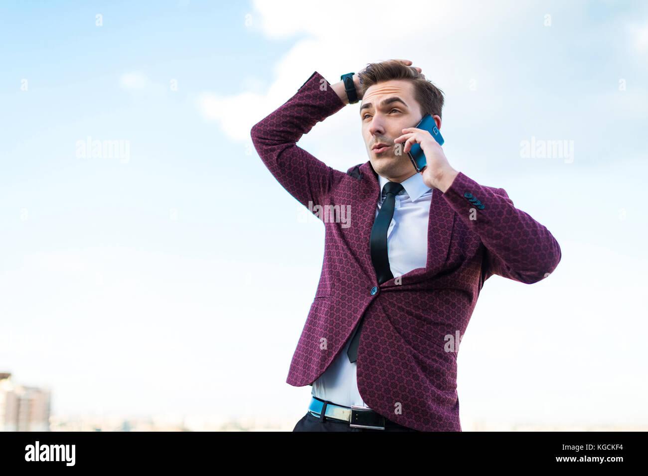 Giovane imprenditore gravi in tuta rossa e camicia con cravatta stand o Immagini Stock