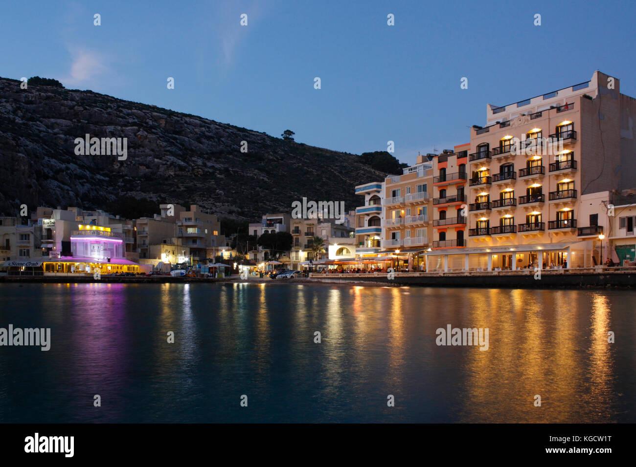 Il villaggio sul mare di Xlendi (pronunciato Shlendy) a Gozo, Malta, al tramonto, con lungomare alberghi e ristoranti Immagini Stock