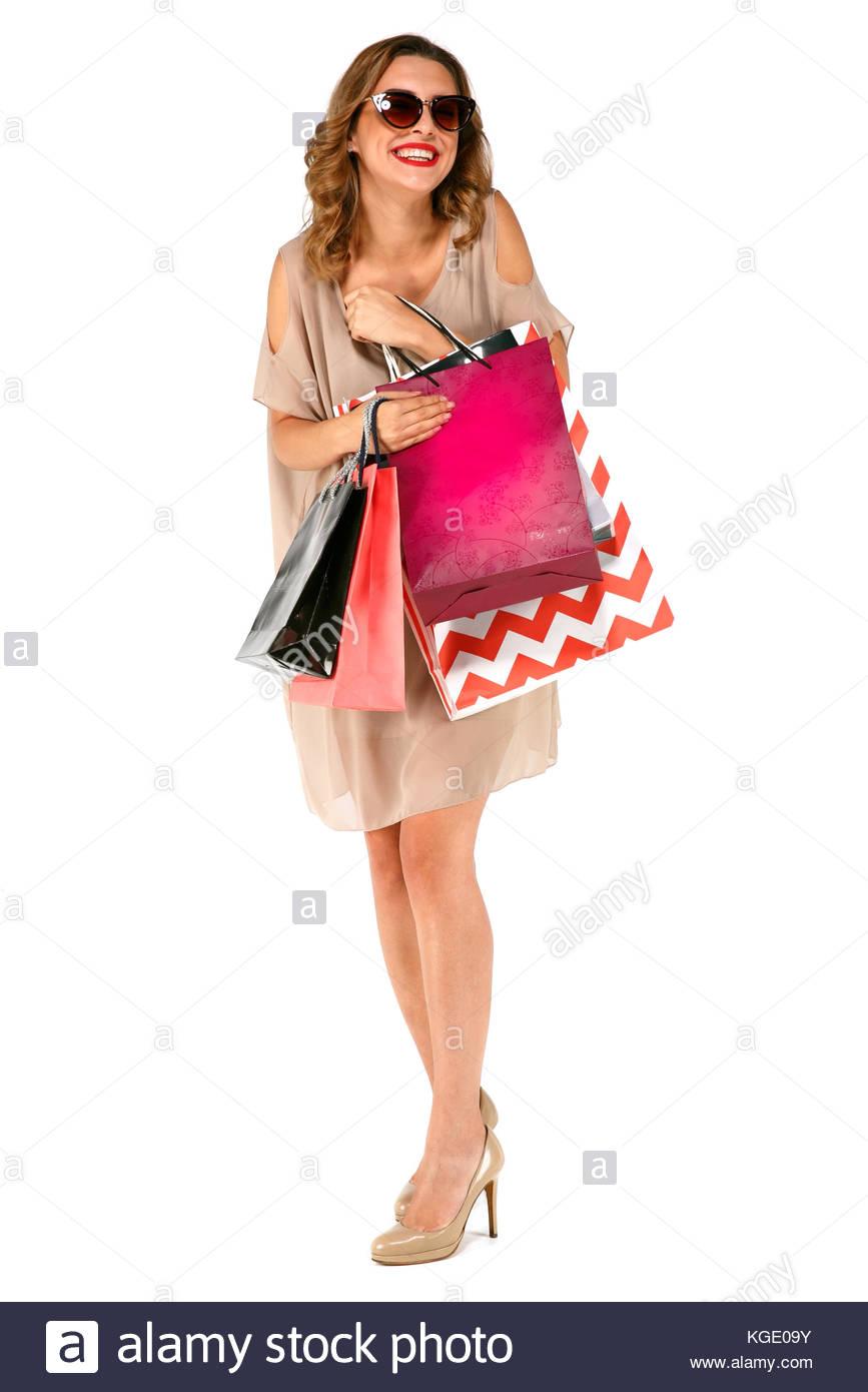 3c39dafdf6d3 Incredibile bruna giovane donna in abiti estivi indossando occhiali da sole  in posa con le borse della spesa e guardando la telecamera su sfondo bianco  ...