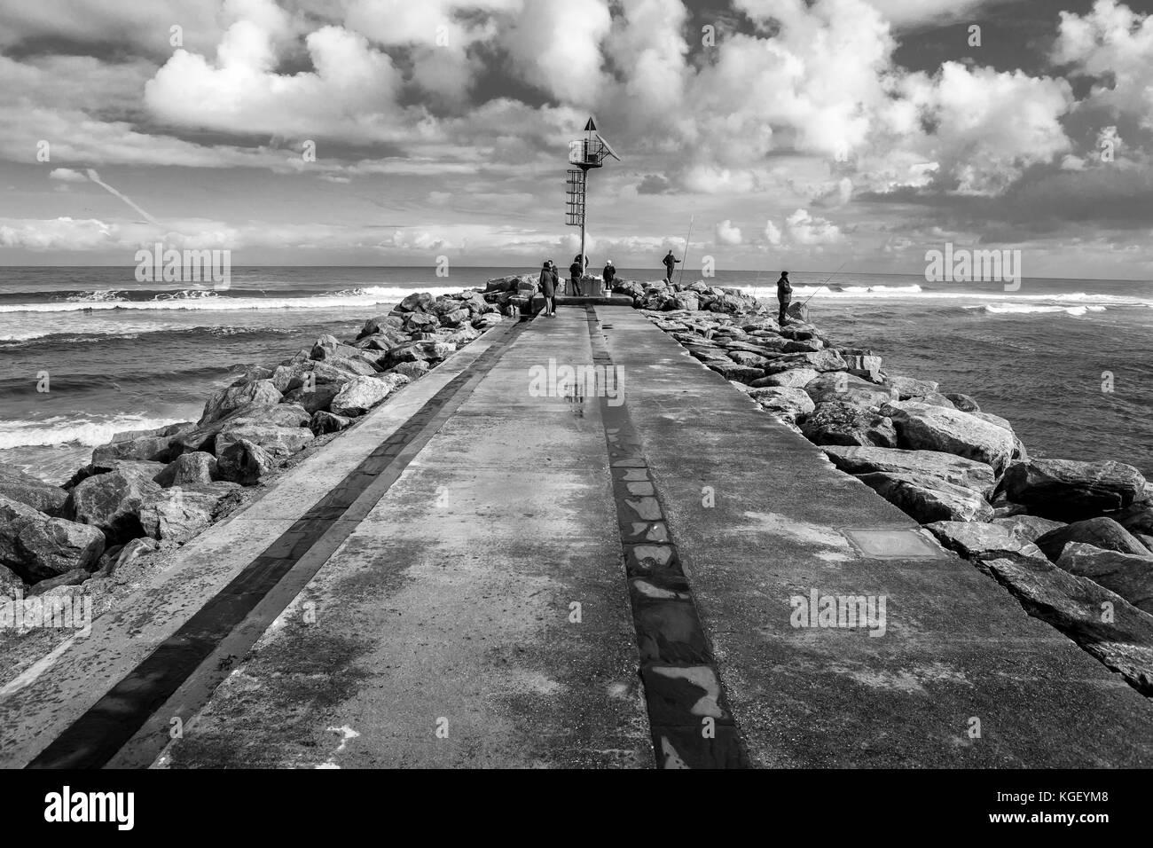 Un lontano gruppo di persone su un molo un giorno nuvoloso Immagini Stock
