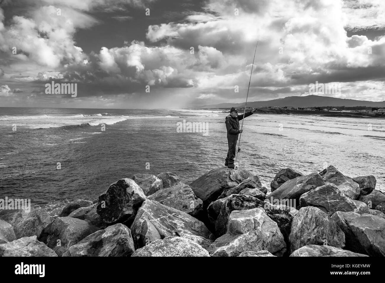 Fisherman pesca un giorno di tempesta con il mare in background Immagini Stock