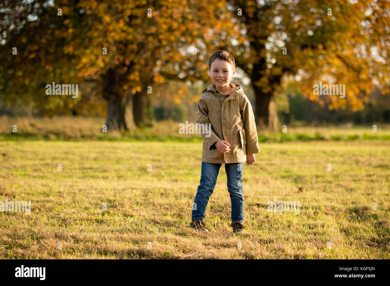 Ragazzo passeggiate nel parco castletown godendo belle novembre meteo con gli alberi decidui versando loro foglie Immagini Stock