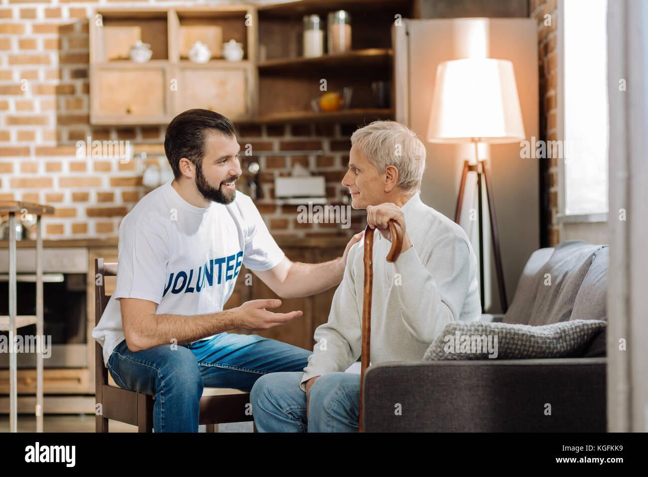 Giovani volontari attento che raccontano le ultime novità ad un uomo anziano Immagini Stock