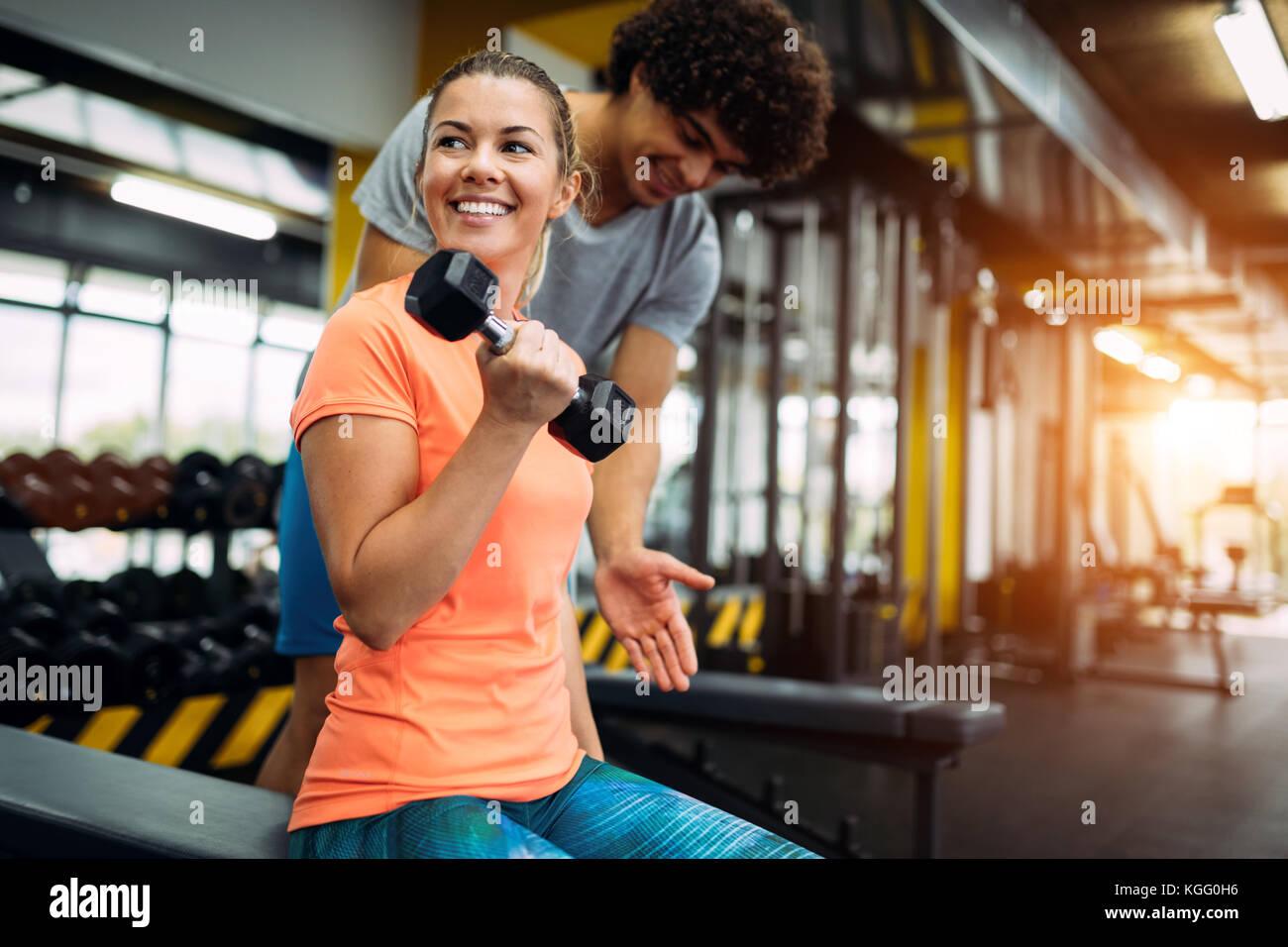 Giovane bella donna facendo esercizi con personal trainer Foto Stock