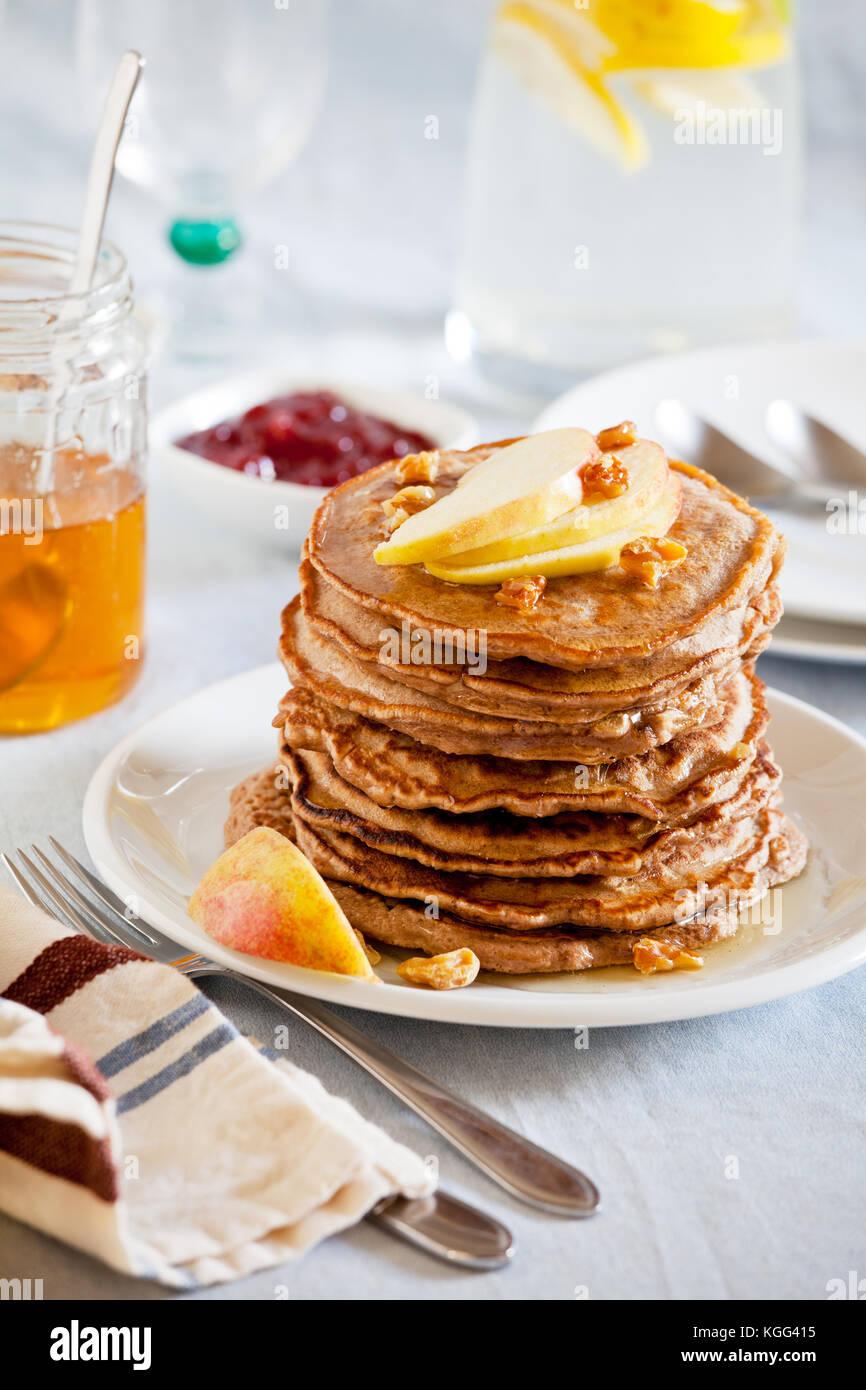 Pila di fatti in casa di grano intero pancake con frutta e noci Immagini Stock