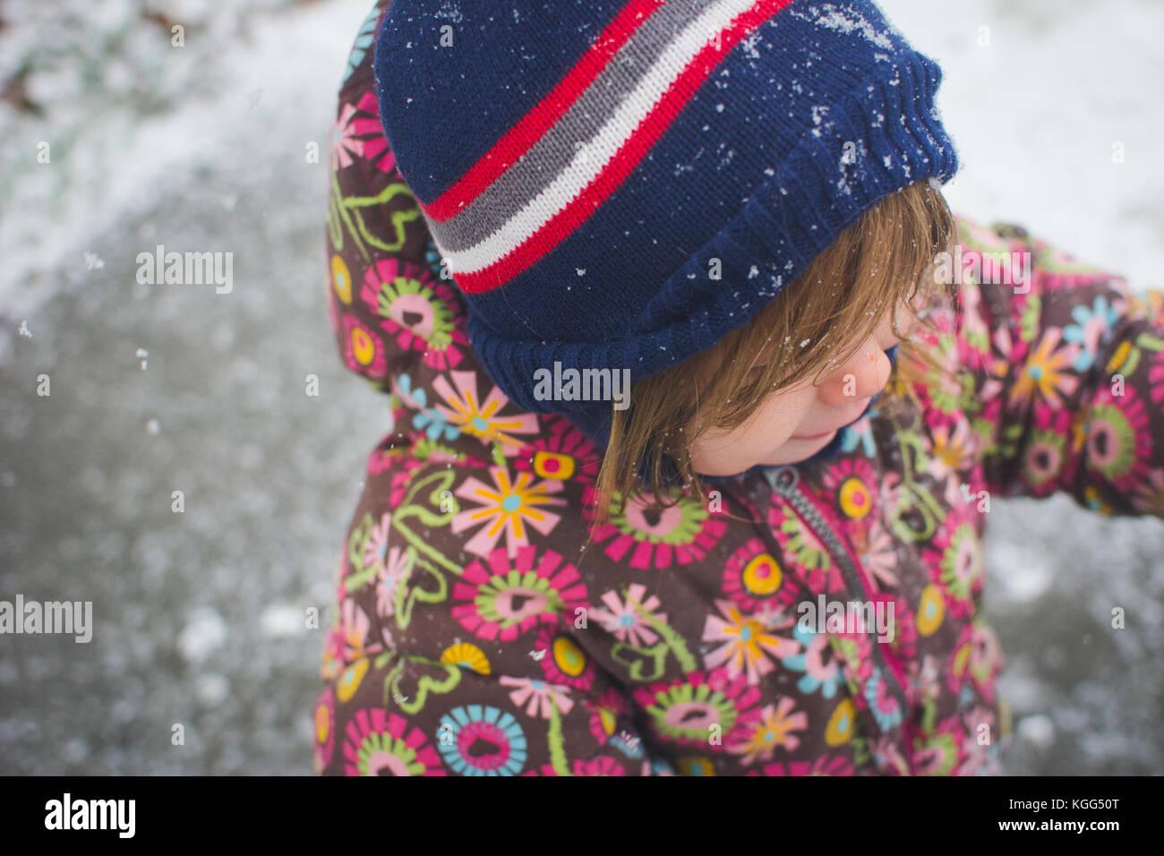 Un bimbo sta al di fuori di indossare abbigliamento invernale con neve intorno a lei. Immagini Stock