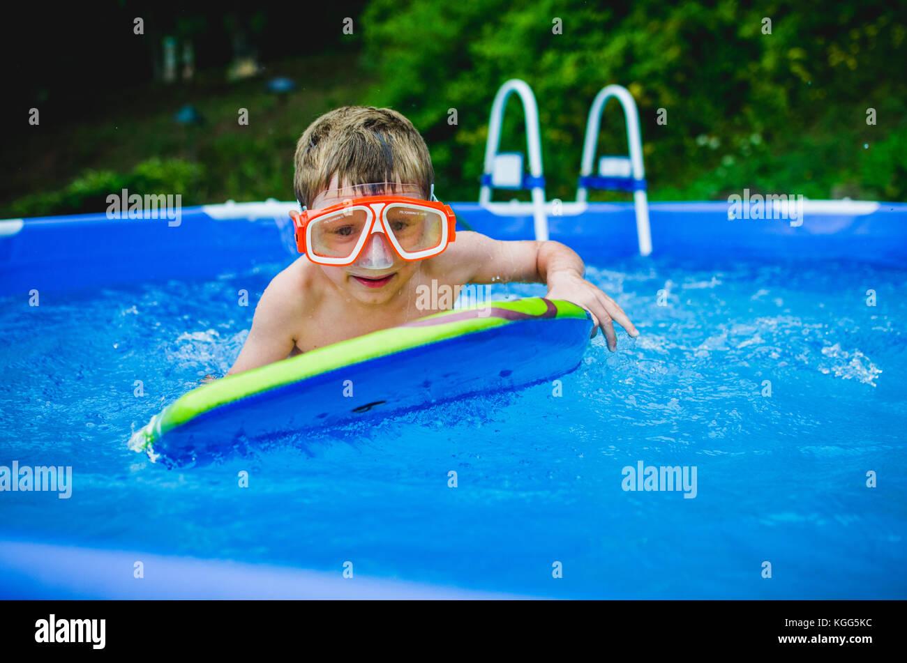 8-9 anni di giocare su un boogie board in una piscina in estate. Immagini Stock