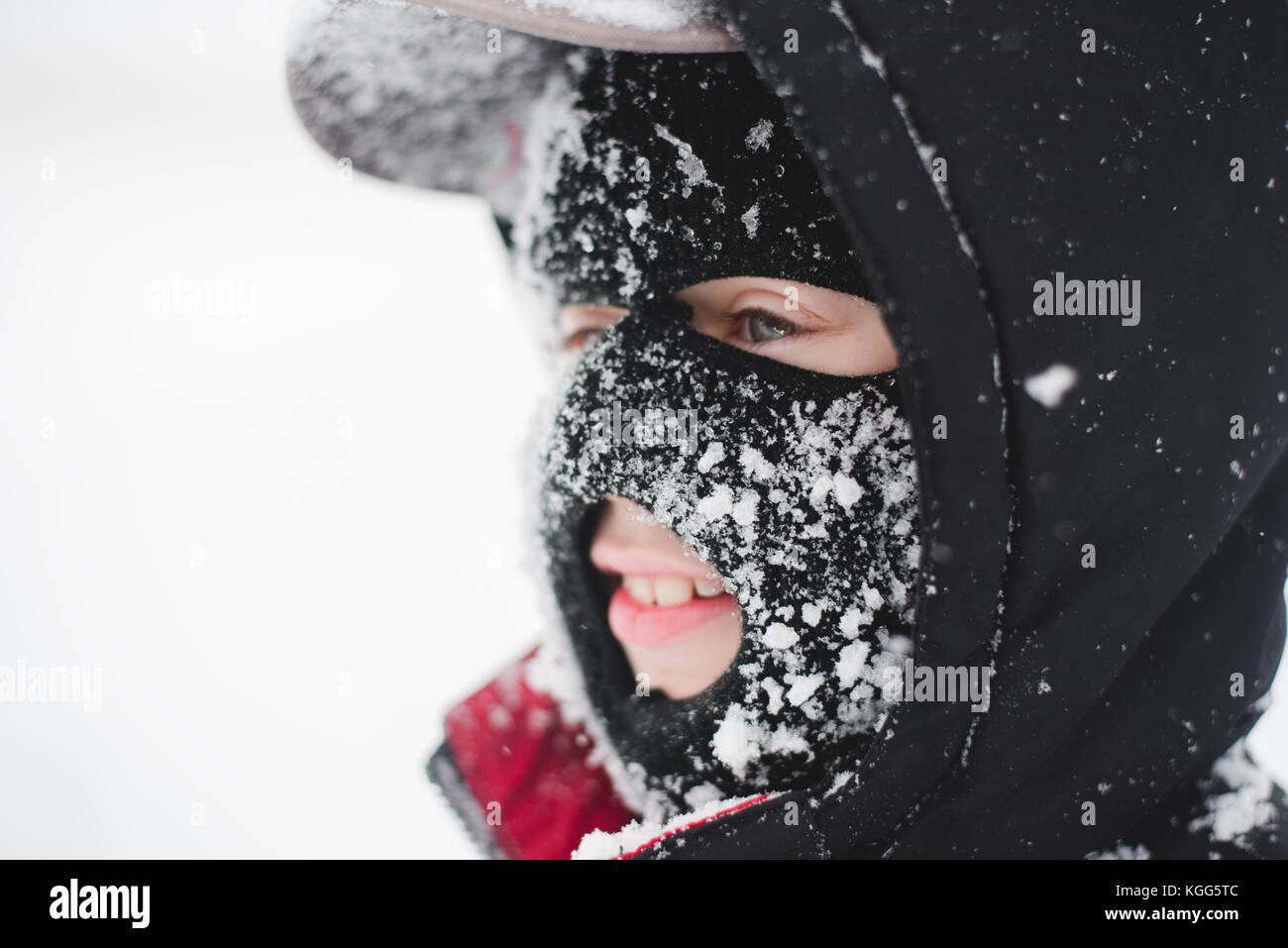 Bambino che indossa una maschera da sci coperta di neve Immagini Stock