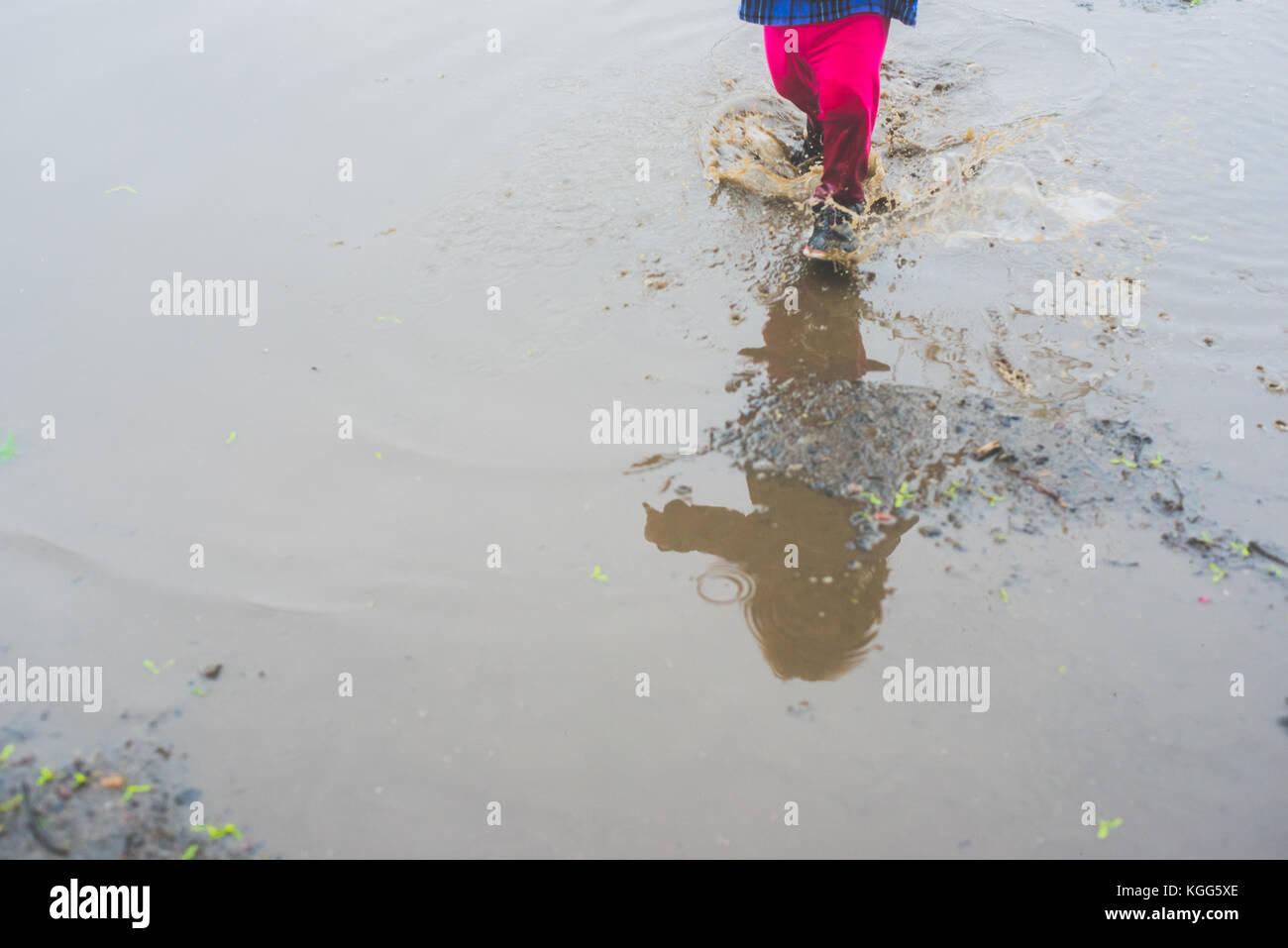 Bambino a camminare in una pozza di fango Immagini Stock