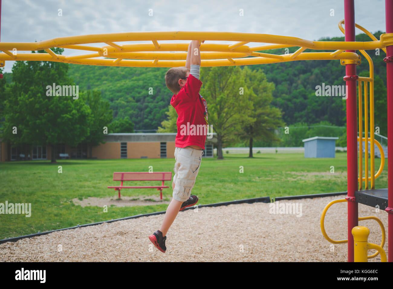 11-12 anni arrampicata su barre ad un parco giochi Immagini Stock