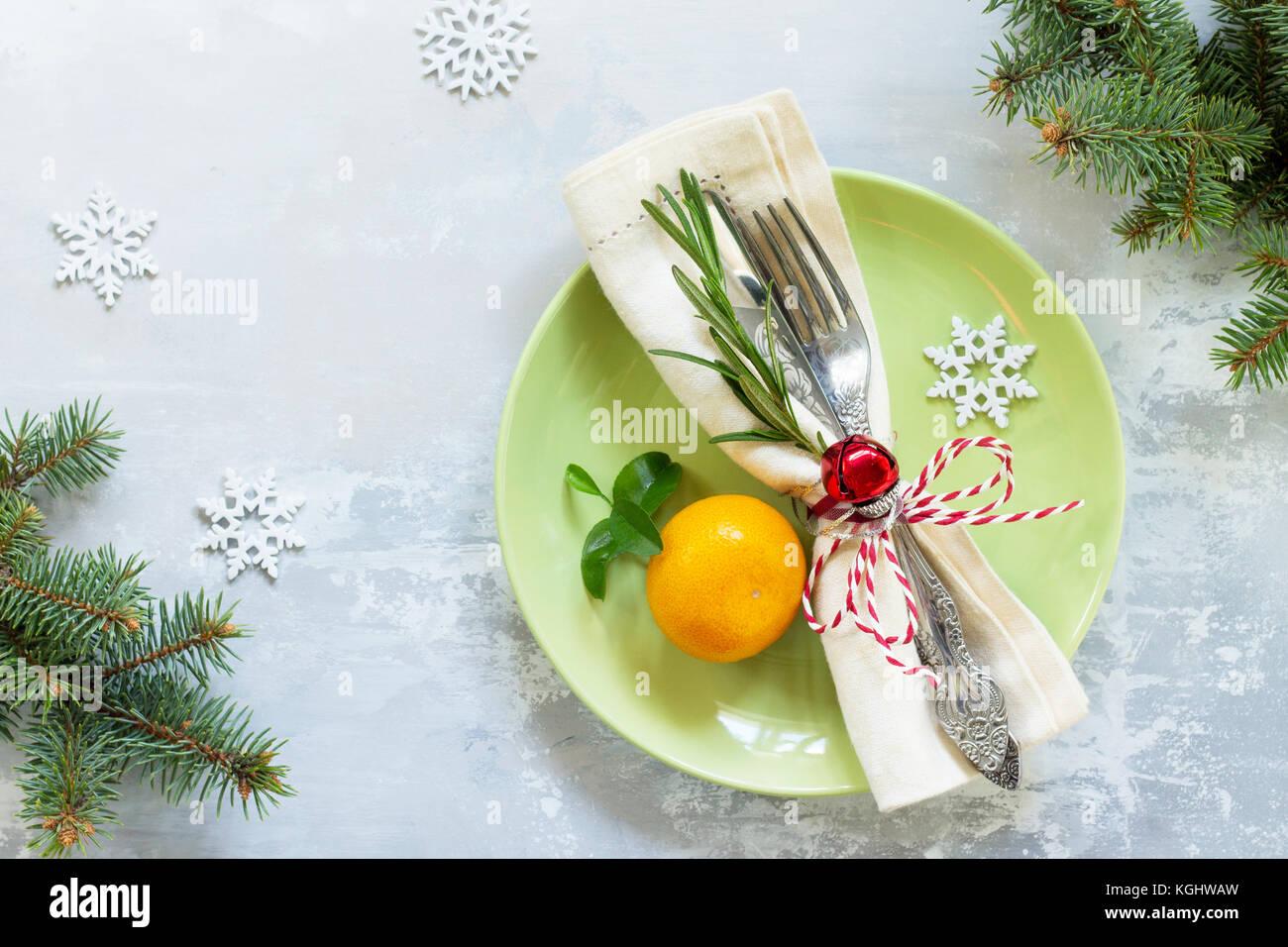 Holiday sfondo. decor tavola di natale su pietra o ardesia background. piastra verde, posate e decorazioni. vista Immagini Stock