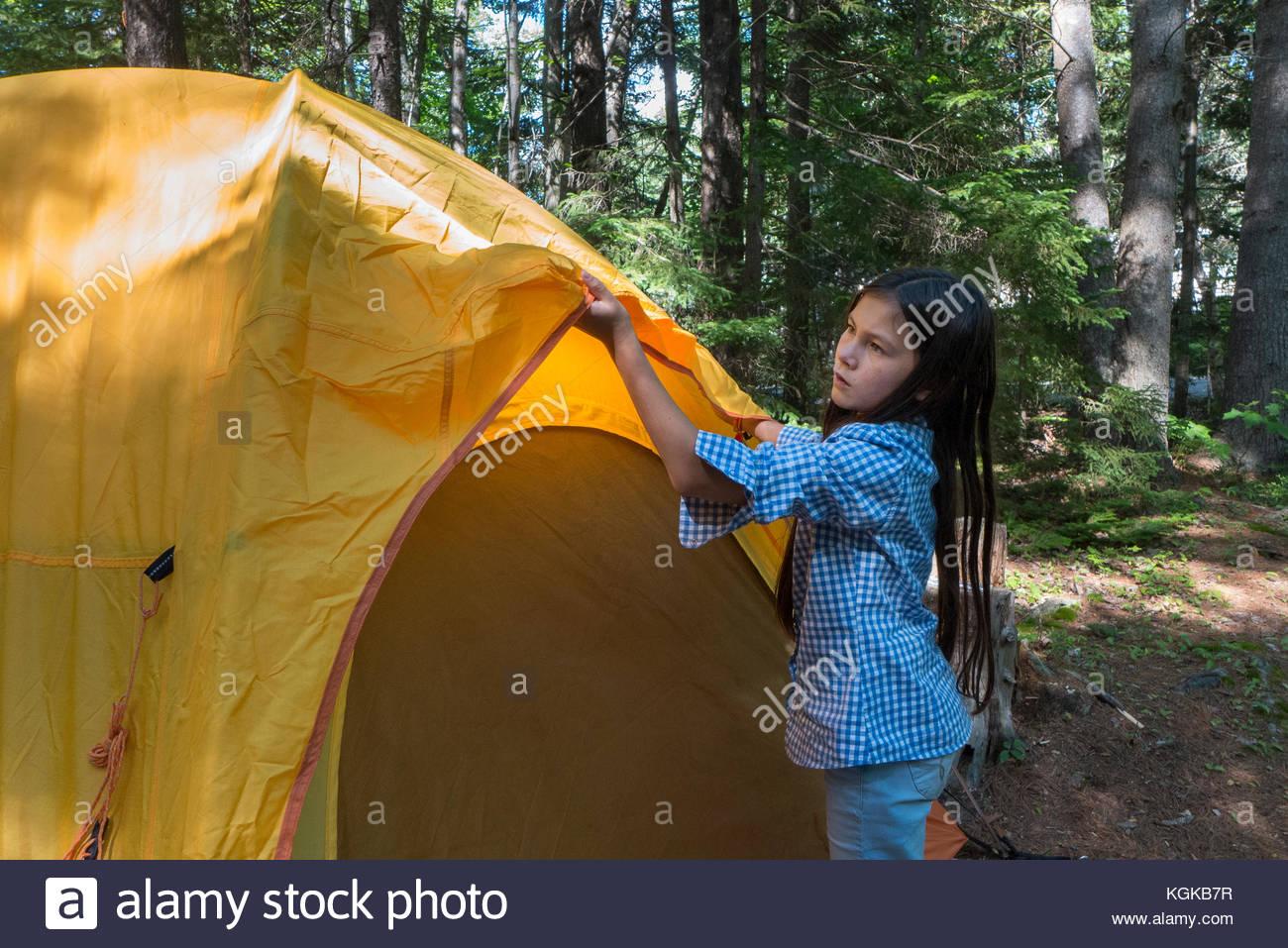 Una giovane ragazza imposta una tenda in un campeggio. Immagini Stock