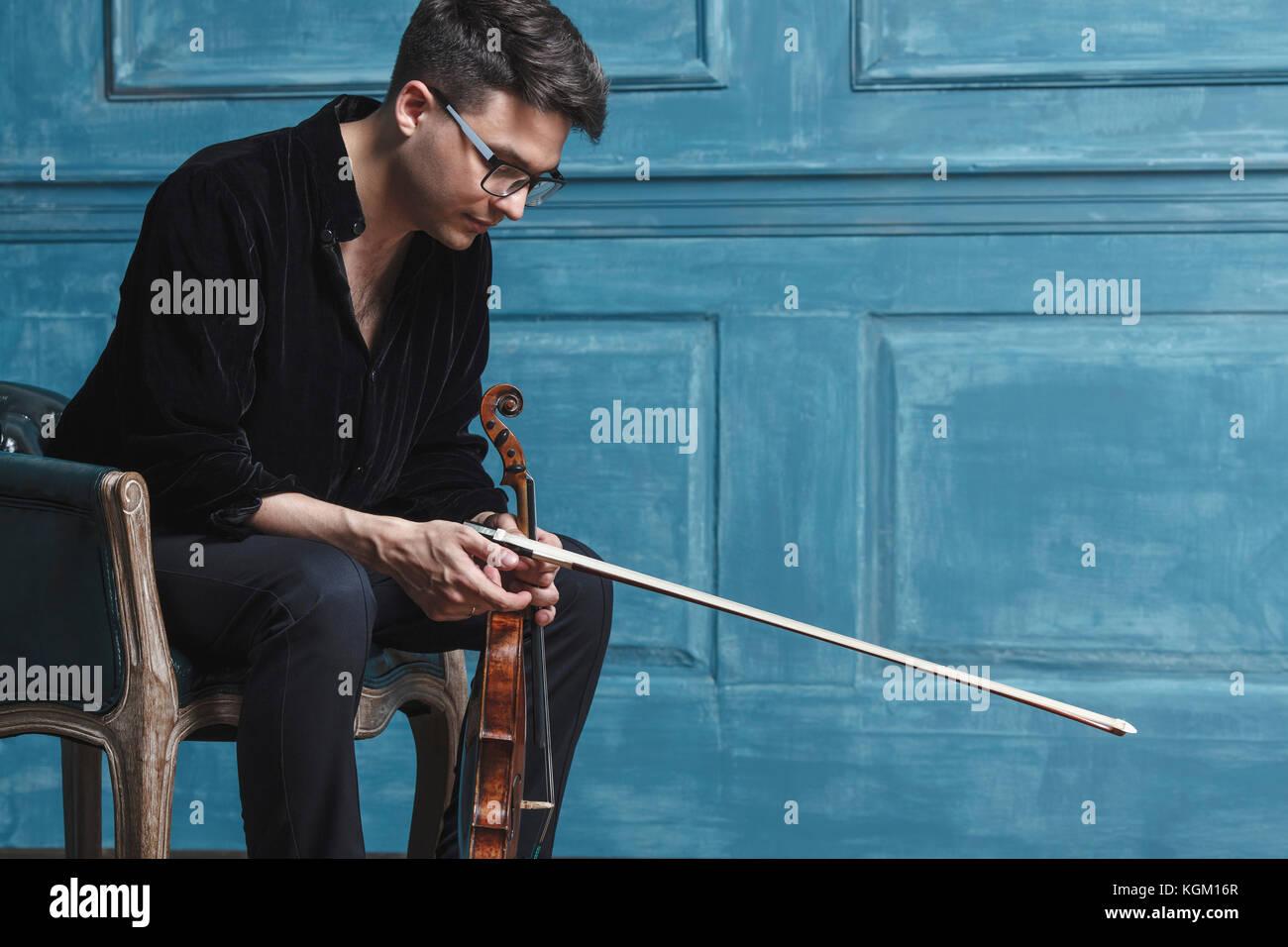 Giovane Azienda violino mentre è seduto sulla sedia di parete blu Immagini Stock