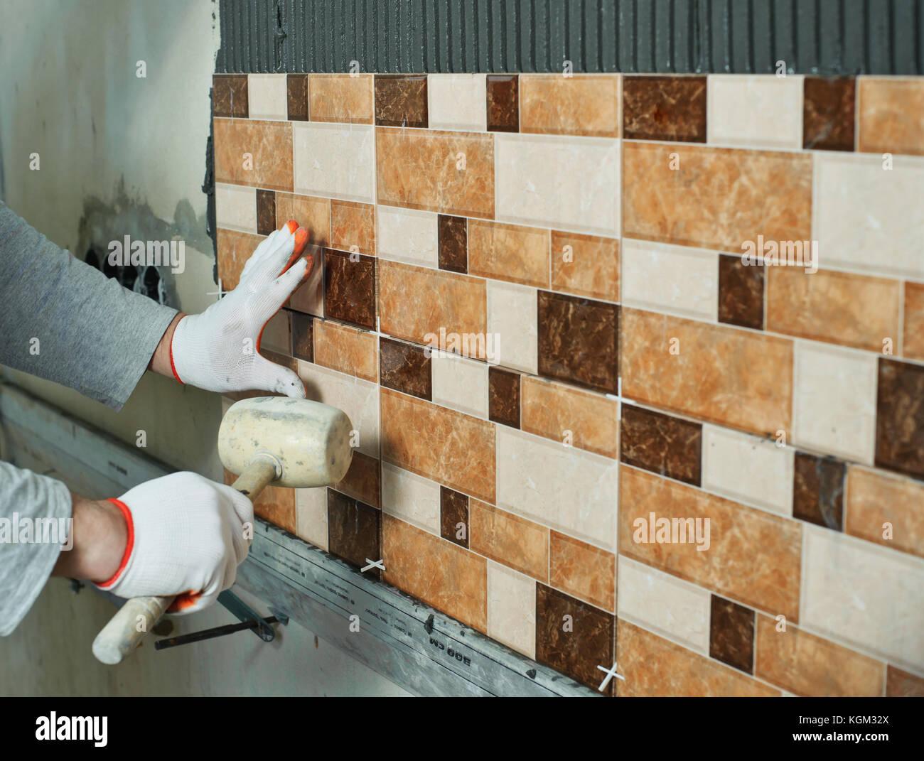La posa di piastrelle di ceramica. installatore a bussare sulle