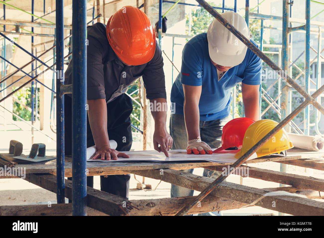 Concetti di costruzione, ingegnere e architetto lavora al sito in costruzione con blueprint, effetto vintage Immagini Stock