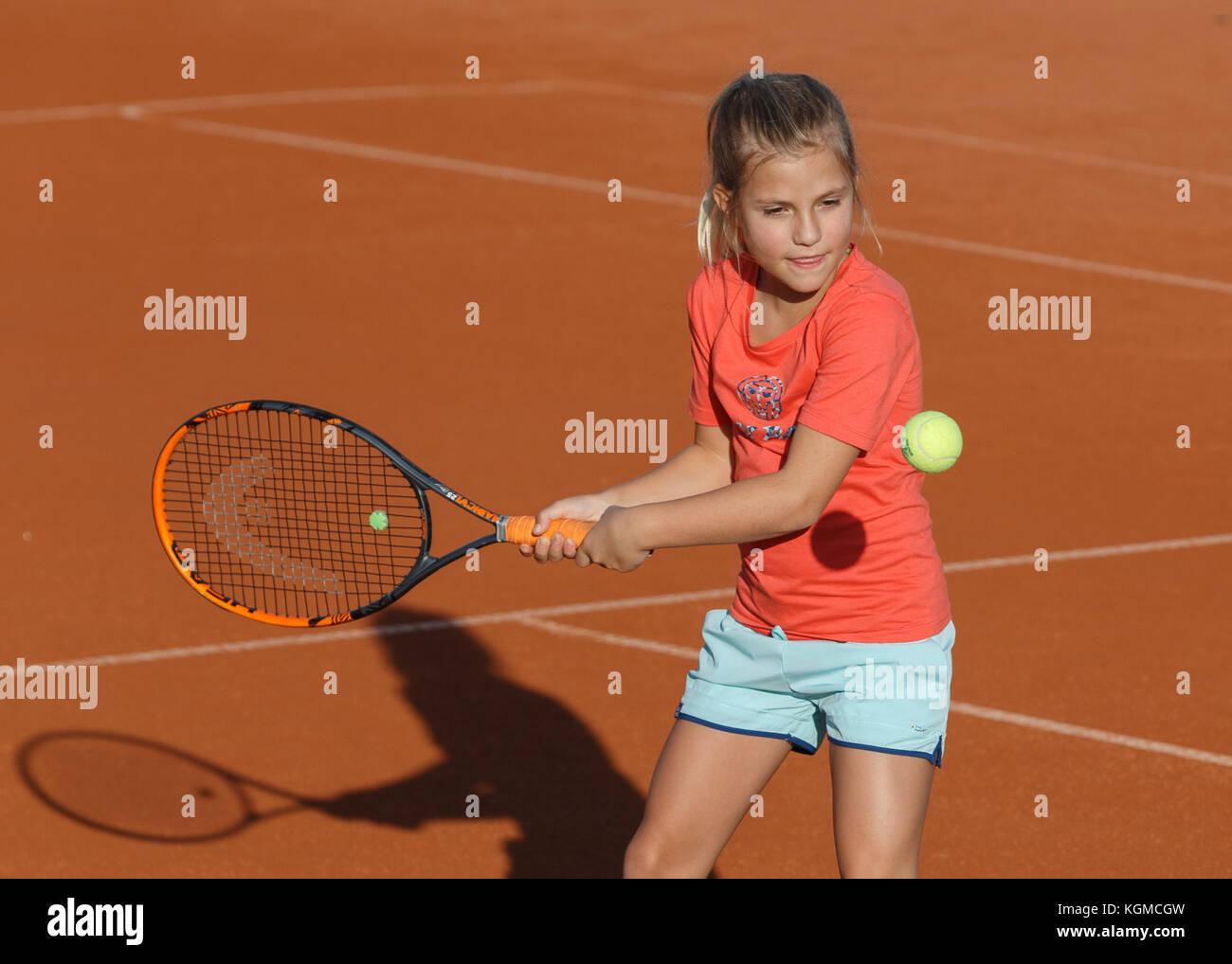 Ragazza giovane (8)0 giocare a tennis Immagini Stock