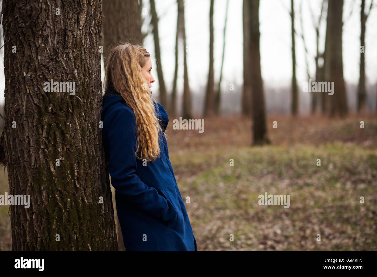 Lonely woman standing nella foresta in inverno Immagini Stock