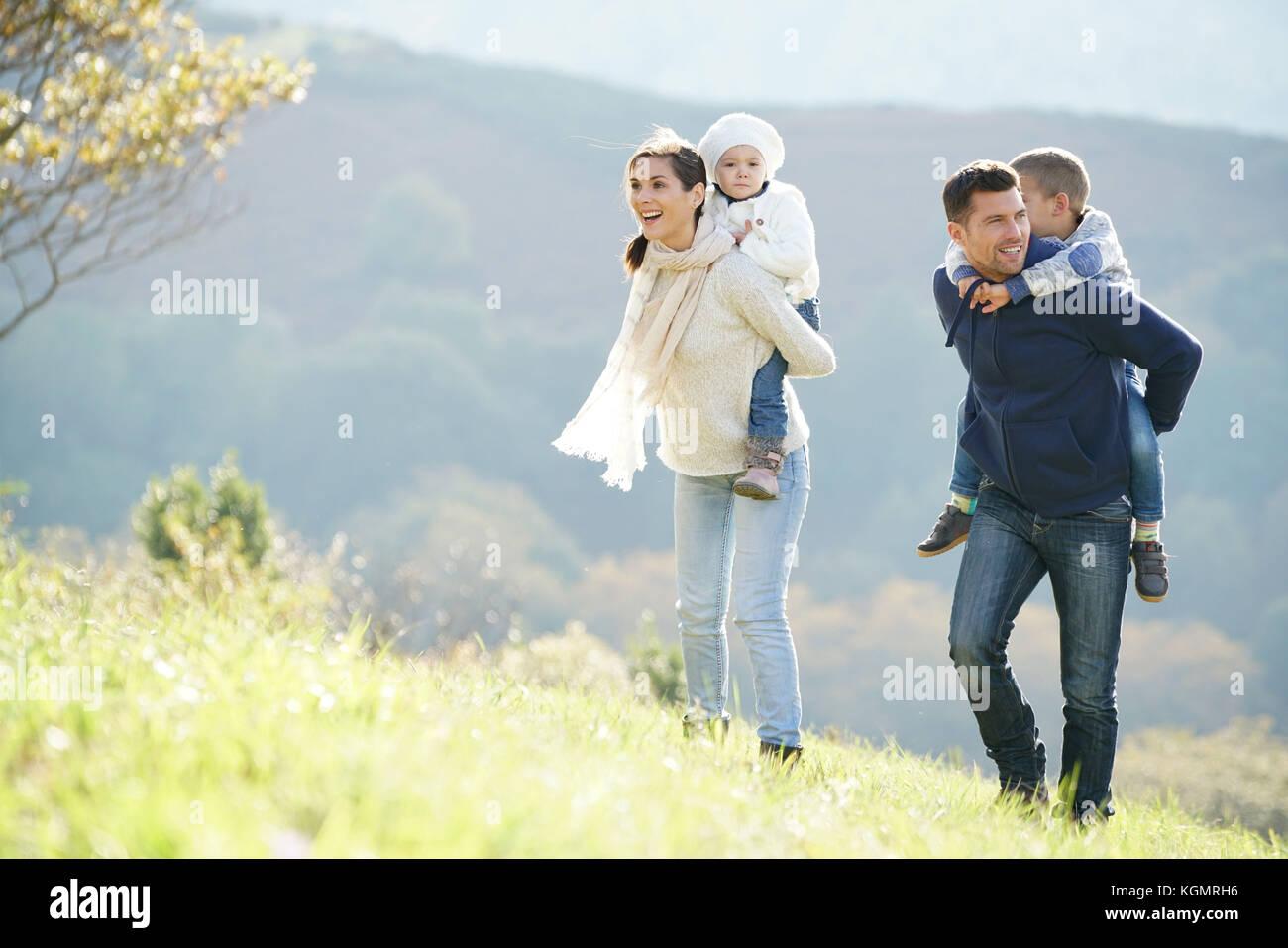 La famiglia felice passeggiate in campagna autunnale di week-end Immagini Stock