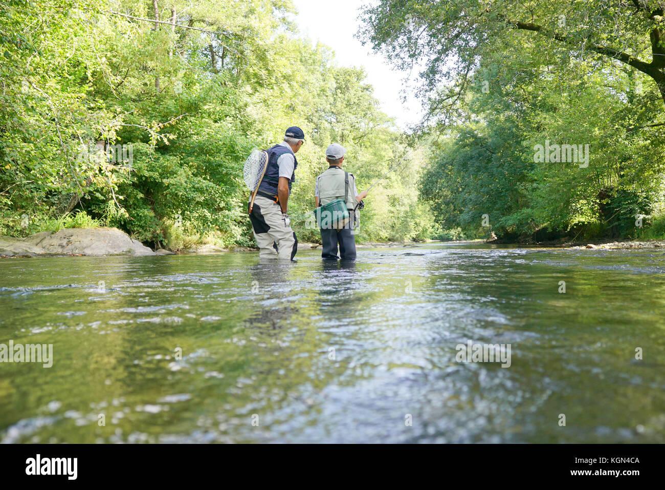 Padre e figlio di pesca a mosca nel fiume Foto Stock