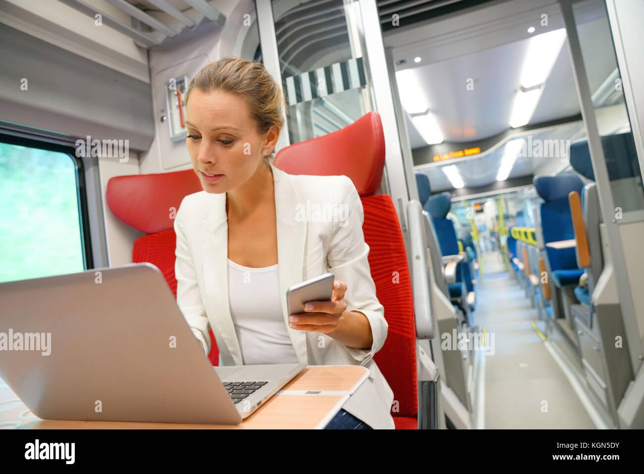 Imprenditrice nel treno lavorando su laptop e parlando al telefono Immagini Stock