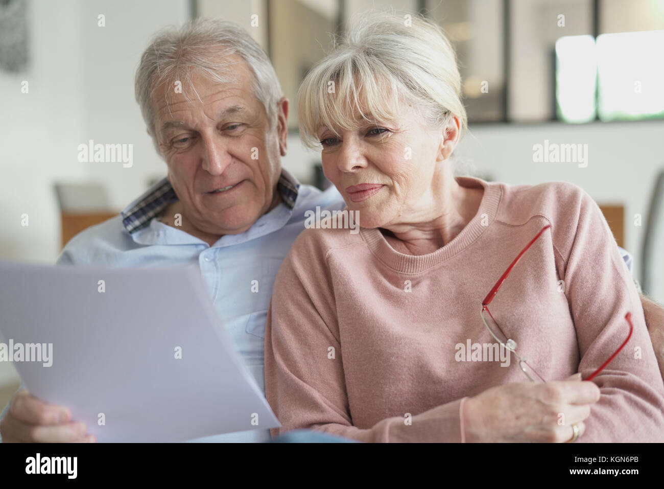 Coppia senior in divano la lettura di documenti ufficiali Immagini Stock
