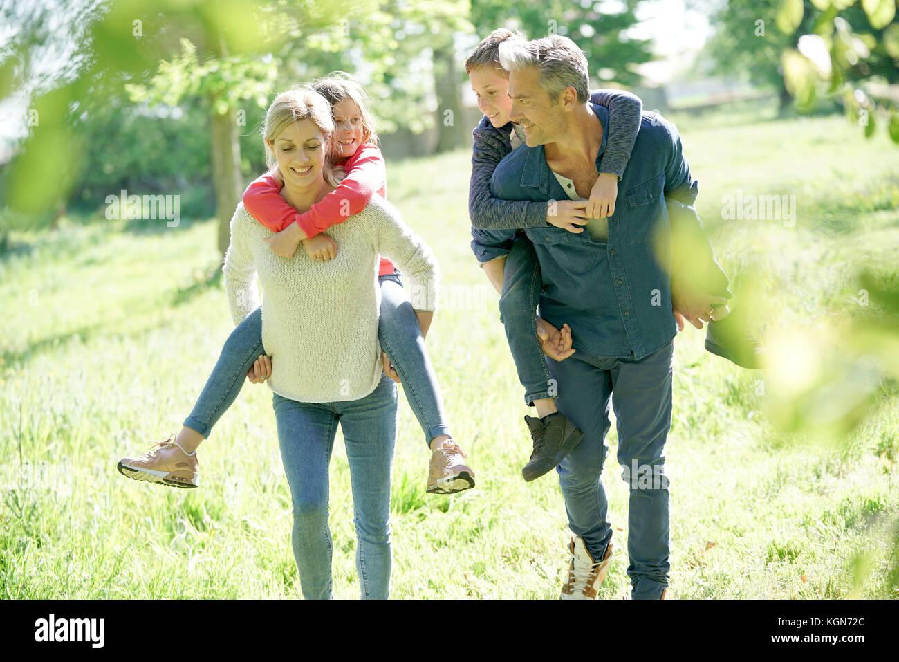 I genitori dando piggyback ride per bambini in campagna Immagini Stock