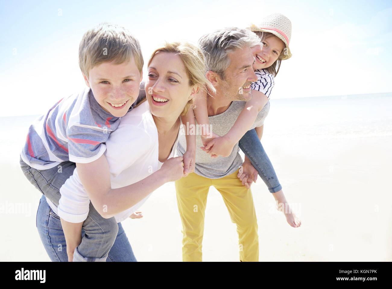 I genitori dando piggyback ride per bambini in spiaggia Immagini Stock