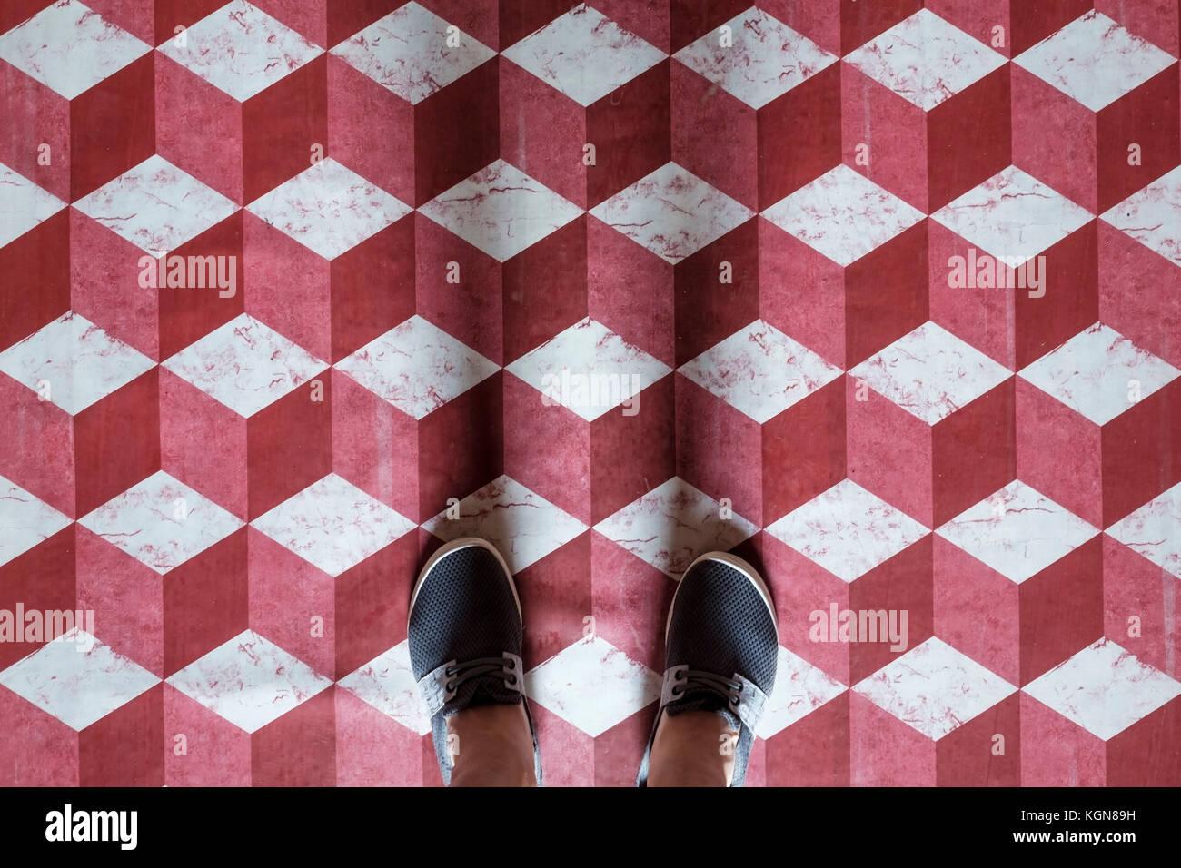Selfie di piedi con scarpe sneaker sul modello di arte pavimento