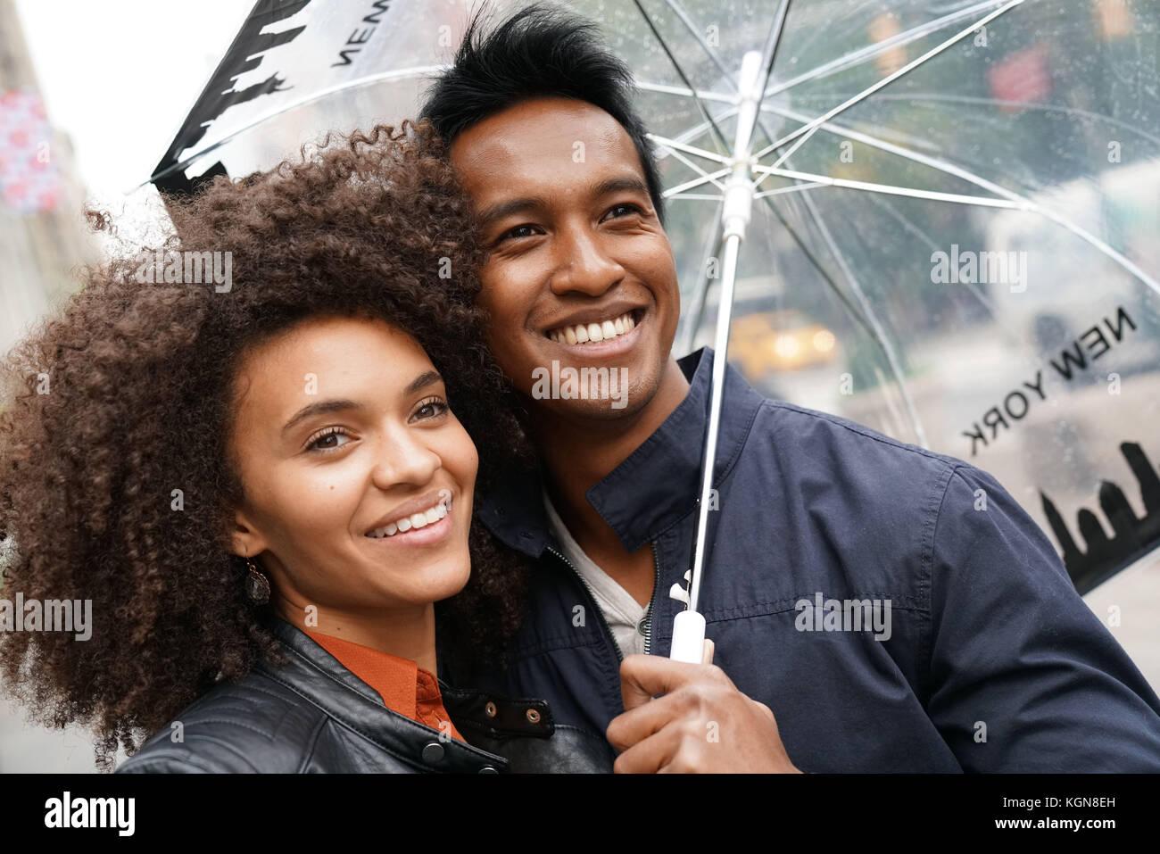 Coppia etnica a piedi nella città di new york street sul giorno di pioggia Immagini Stock