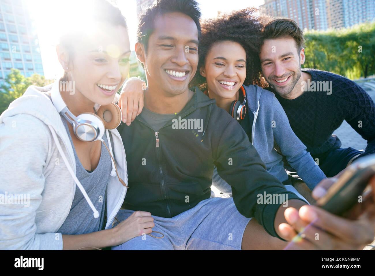 Gruppo di amici in abito casual tenendo selfie foto con lo smartphone Immagini Stock