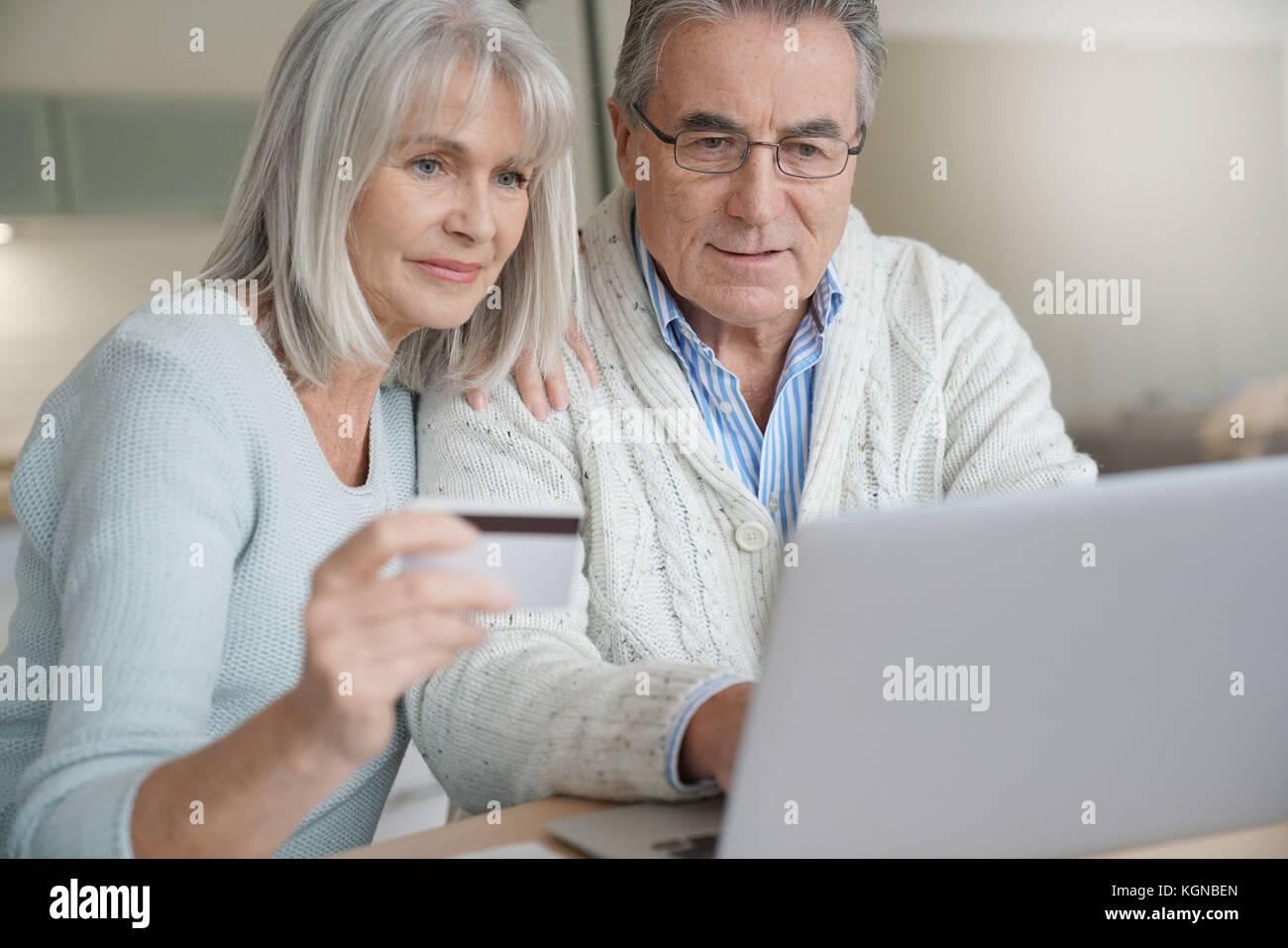 Coppia senior acquisti su internet con carta di credito Immagini Stock