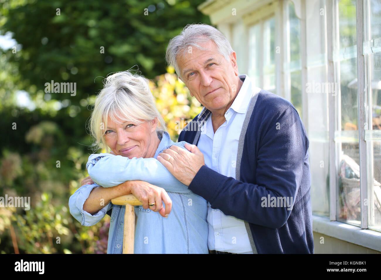 Coppia senior in piedi da serra in giardino Immagini Stock
