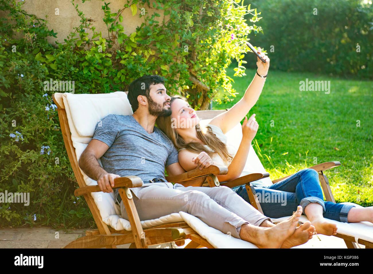 Coppia giovane tenendo selfies Immagini Stock