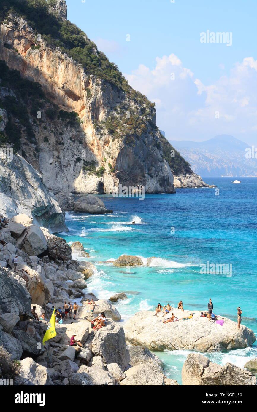 I turisti di nuoto e di balneazione a Cala luna beach in Sardegna, Italia Immagini Stock