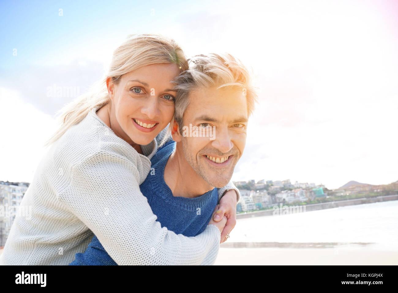 L uomo dando piggyback ride per donna in spiaggia Immagini Stock